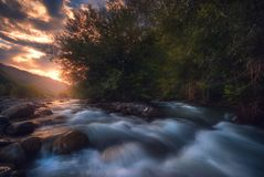 Salida del sol sobre el río rápido de la montaña imagen de archivo