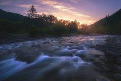 Salida del sol sobre el río rápido de la montaña foto de archivo