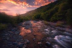 Salida del sol sobre el río rápido de la montaña imagenes de archivo
