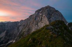 Salida del sol sobre la montaña de Mangart con el cielo rojizo dramático, Julian Alps, paso de Mangart, Eslovenia, parque naciona fotografía de archivo libre de regalías