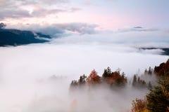 Salida del sol sobre la niebla en las montañas Fotos de archivo libres de regalías