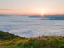 Salida del sol sobre la niebla del mar Paisaje de la montaña del verano foto de archivo