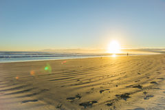 Salida del sol sobre la playa arenosa plana ancha en Ohope Whakatane imagenes de archivo