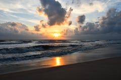 Salida del sol sobre la playa del mar, nublado y la onda Imagenes de archivo