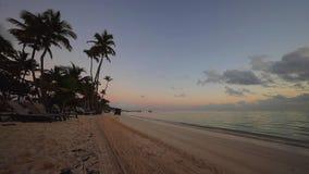 Salida del sol sobre la playa tropical de la isla en Punta Cana, República Dominicana Tractor que limpia el seand almacen de metraje de vídeo