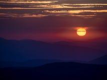 Salida del sol sobre las montañas con el cielo crepuscular Fotos de archivo