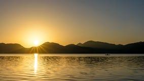Salida del sol sobre las montañas y el lago con el piragüista imagenes de archivo