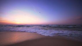Salida del sol sobre las ondas del mar y la playa arenosa almacen de metraje de vídeo