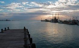 Salida del sol sobre los barcos de pesca de Puerto Juarez Cancun México/barco rastreador y muelles y embarcadero y embarcadero y  Foto de archivo
