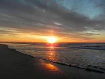 Salida del sol sobre ondas oscuras de la playa Imagen de archivo libre de regalías