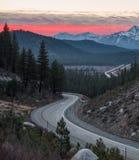 Salida del sol sobre Sierra Nevada según lo visto de un camino con curvas imagen de archivo