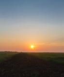 Salida del sol sobre surco y campo Foto de archivo libre de regalías