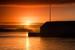 Salida del sol sobre un edificio del embarcadero Foto de archivo