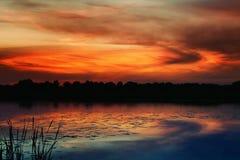 Salida del sol sobre un pequeño lago Fotos de archivo libres de regalías