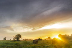 Salida del sol sobre un prado brumoso con los bloques de la paja fotografía de archivo