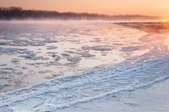Salida del sol sobre un río de congelación cubierto en niebla imagenes de archivo