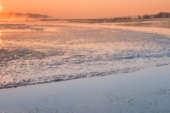 Salida del sol sobre un río de congelación cubierto en niebla foto de archivo