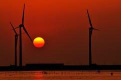 Molino de viento en la puesta del sol imagenes de archivo