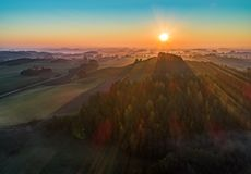 Salida del sol sobre una montaña y un bosque - foto aérea imagen de archivo