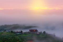 Salida del sol soleada en un campo hermoso Niebla apacible sobre el chalet Imagen de archivo libre de regalías