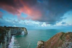 Salida del sol tempestuosa rosada sobre los acantilados en el océano Foto de archivo libre de regalías