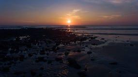 Salida del sol temprana en la playa de piedra negra Fotos de archivo