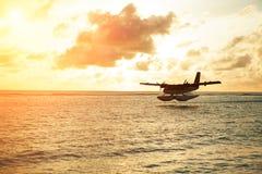 Salida del sol del verano con el hidroavión Hidroavión del aterrizaje en la costa Imagen de archivo libre de regalías