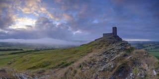 Salida del sol del verano en Brentor showning la iglesia de San Miguel encima del tor con las nubes dram?ticas del tiempo de duch fotografía de archivo