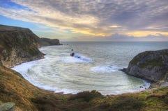 Salida del sol vibrante sobre el océano y la ensenada abrigada Imagen de archivo libre de regalías