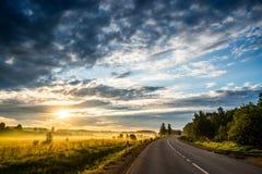 Salida del sol y carretera de asfalto Fotos de archivo