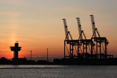 Salida del sol y las grúas portuarias Imagenes de archivo