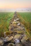 Salida del sol y pared de piedra que desaparecen en la niebla, HDR Foto de archivo libre de regalías