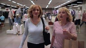 Salida satisfecha sonriente de las mujeres de la tienda de la ropa metrajes