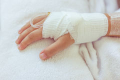 Saline intravenous (iv) drip in a child's patient hand. Royalty Free Stock Images