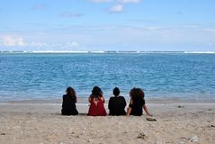 Saline les Bains, beach Reunion Island. Saline les Bains, white coral beach in reunion Island, France, Africa. Sunny day. Four young girls watching the coral royalty free stock photo