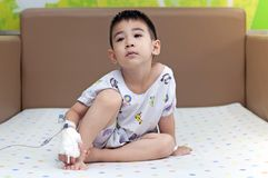 Saline Solution On Hand of Patients Child sit on bed feel boring healthy nursing care of hospital life insurance. Sick child bandage covered hand saline sit on royalty free stock photo