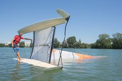 Salior trying to right catamaran after capsize Royalty Free Stock Images