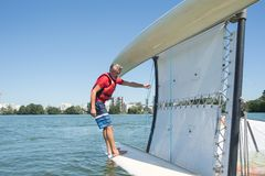 Salior trying to right catamaran after capsize. Salior trying to right his catamaran after capsize royalty free stock images