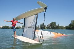 Salior trying to right catamaran after capsize. Salior trying to right his catamaran after capsize royalty free stock image