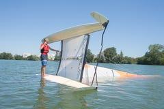 Salior trying to right catamaran after capsize. Salior trying to right his catamaran after capsize stock photos