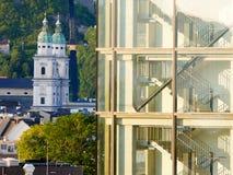 Salisburgo/Austria - 2 giugno 2019: Contrasto architettonico con torri le vecchie di chiesa e una costruzione moderna fotografie stock libere da diritti