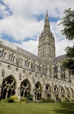 Salisbury Cathedral, England. View of Salisbury Cathedral from the courtyard looking up at the tower with spires, window, arches, carved stone and clouds with Royalty Free Stock Photo