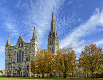 Salisbury Cathedral on a Sunny Autumn Day. A view of the exterior west entrance of Salisbury Cathedral and tower, photographed in Autumn with the trees beside Stock Photo