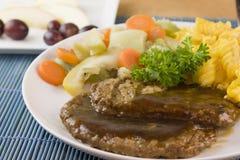Salisbury steak detail. Detail of salisbury steak patties with steam vegetables and spiral macaroni Stock Photos