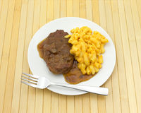 Salisbury steak meal on a plate with a fork. A meal of salisbury steak with gravy macaroni and cheese on a plate with a fork atop a wood place mat royalty free stock images