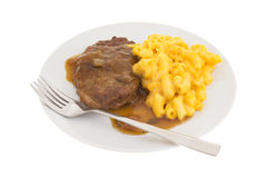 Salisbury steak meal on a plate with a fork. A meal of salisbury steak with gravy macaroni and cheese on a plate with a fork isolated on a white background stock photos