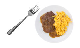 Salisbury steak meal on a plate with a fork. Top view of a meal of salisbury steak with gravy macaroni and cheese on a plate with a fork to the side isolated on stock photos