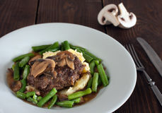Salisbury steak. A plate of salisbury steak with mashed potatoes, green beans and mushrooms royalty free stock image