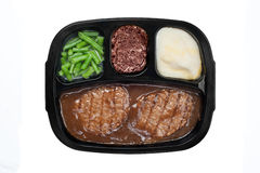 Salisbury TV dinner. An unhealthy Salisbury steak TV dinner with gravy, mashed potatoes and a brownie dessert in a plastic tray isolated on white Stock Photos