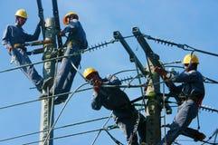 Salita asiatica alta, lavoro dell'elettricista sul palo elettrico Immagini Stock Libere da Diritti